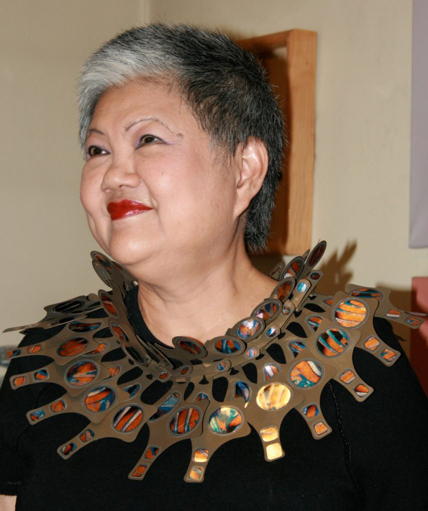 "One of my earliest pieces ""Podium Neck Wreath Gold"" originally in the collection of Tuan Lee now in the Museum of Fine Arts in Boston, USA. A gold coloured neck piece of regular mechanical shapes with iridescent inlay worn by the owner a Singaporean lady with short hair bright red lipstick and a black top."