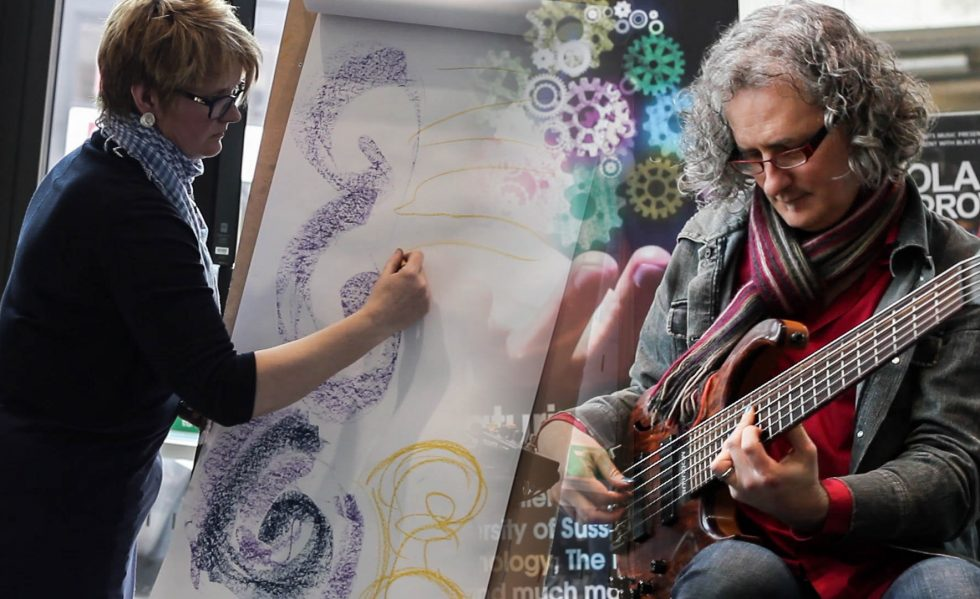 Poppy Porter and Steve Lawson perform Illuminated Loops she draws a large purple swirl on a roll of paper and he plays a six string bass while wearing a colourful scarf
