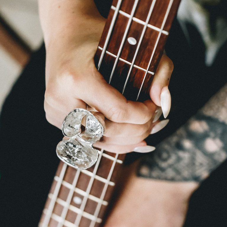 A female hand holds the neck of a bass guitar while wearing a huge statement silver ring she has a blackwork wrist tattoo