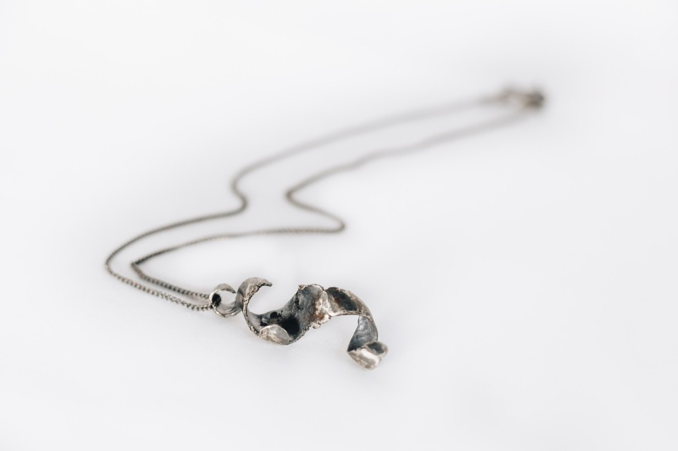 twisted and blackened Silver Pendant on a fine curbchain on a white background