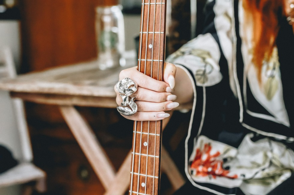 A female hand holds the neck of a bass guitar while wearing a huge statement silver ring