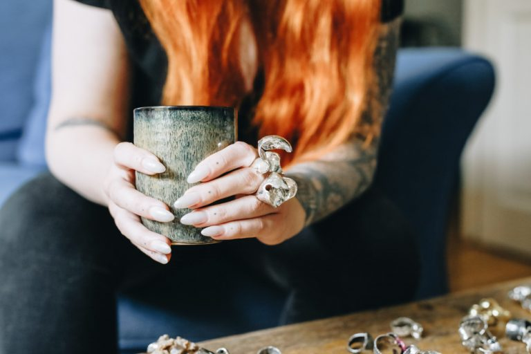 a red haired female model with long white nails holds a handleless coffee cup while wearing a huge statement silver ring