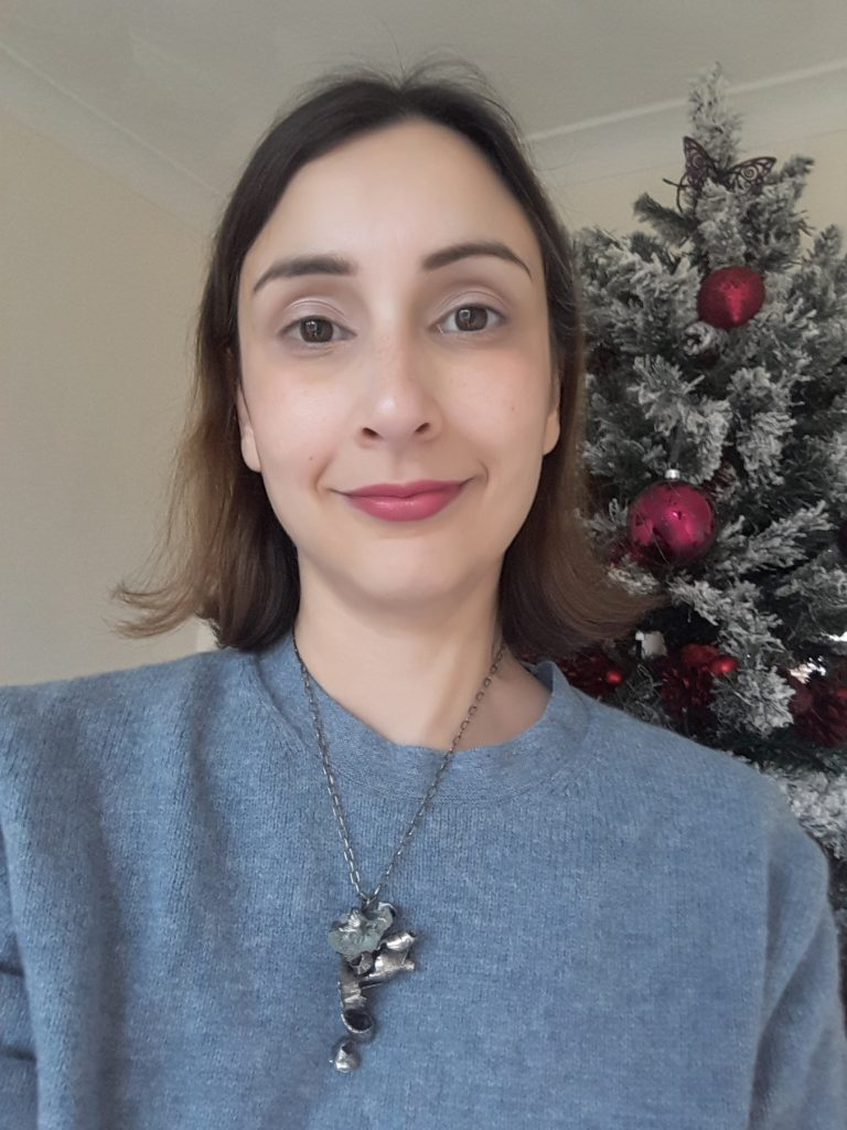 Aquamarine necklace being modeled by woman in front of christmas tree