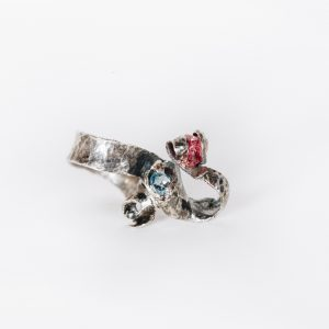 Pink Tourmaline and Blue Topaz Ring in silver with an oxixised finish. crackled texture to the silver the natural pink tourmaline and faceted blue topaz are entwined in tendrils of silver above the ringshank.