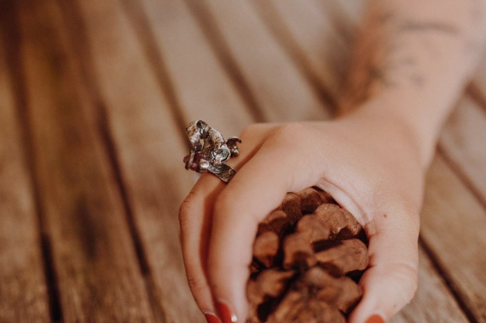 models hand holding a pine cone with orange nail polish wears a Pink Tourmaline and Blue Topaz Ring in silver with an oxixised finish. crackled texture to the silver the natural pink tourmaline and faceted blue topaz are entwined in tendrils of silver above the ringshank.