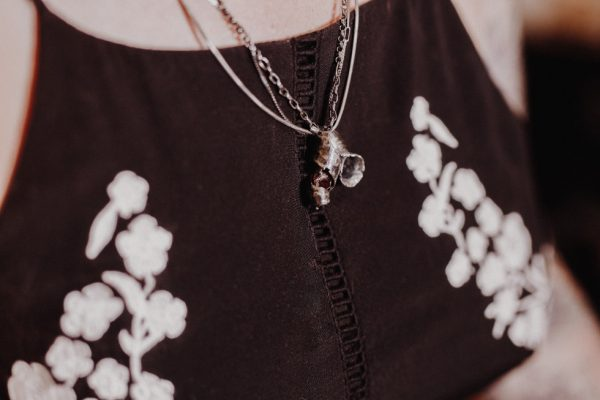Model in a black dress with white flowers wears Natural Garnet Necklace hand forged and oxidised silver curled round a rough garnet stone hung from a triple chain made up of a variety of different chains.
