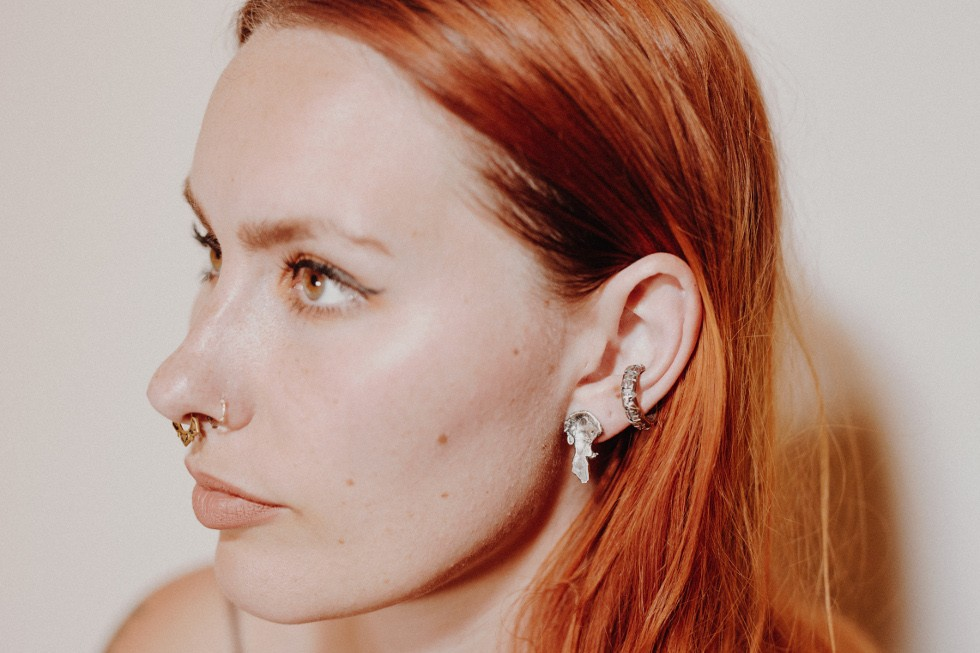 White female model with red hair wears a textured silver stud earring and crosshatched silver ear cuff. Side of face in shot, looking left