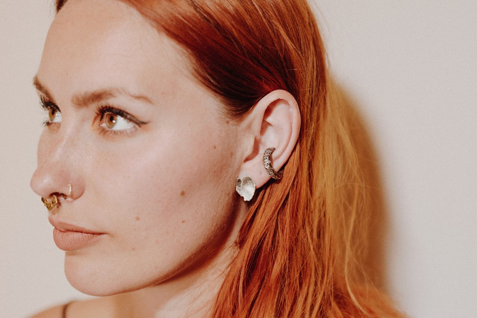 female, white, red haired model facing right wearing Shiny Stud Earrings in silver and a deeply textured silver ear cuff