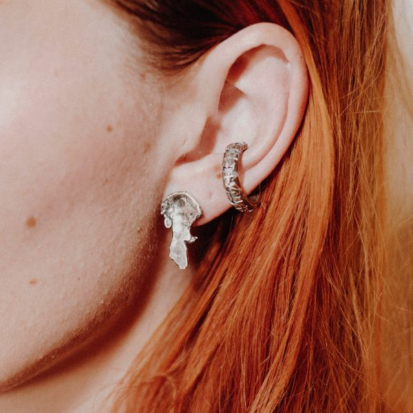 White female model with red hair wears a textured silver stud earring and crosshatched silver ear cuff. Close up image of ear.