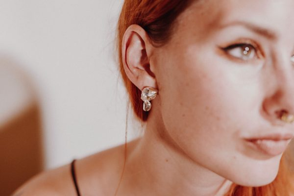 model with red hair wears handmade silver curl earring.