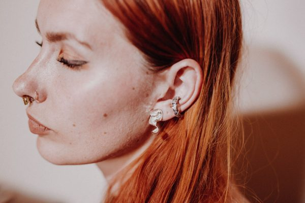 model with red hair wears handmade silver curl earring and textured silver ear cuff.