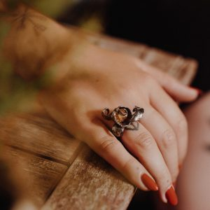 Image of curly silver golden topaz ring on woman's hand.