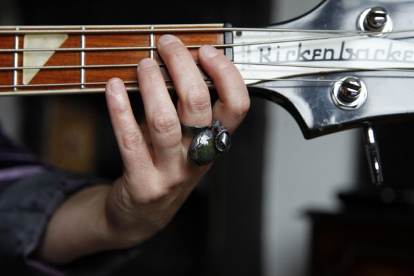 Image of hand modeling large bloodstone cabochon cocktail ring playing a Rickenbacker Bass Guitar