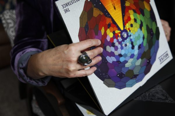 Image of hand modeling large bloodstone cabochon cocktail ring holding vinyl album, Muse's The Resistance