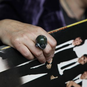 Image of hand modeling large bloodstone cabochon cocktail ring holding vinyl album, Blondie's Parallel Lines
