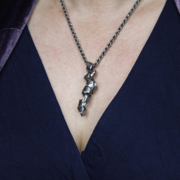 image shows twisted silver necklace with rope chain on a model wearing navy blue v-neck dress