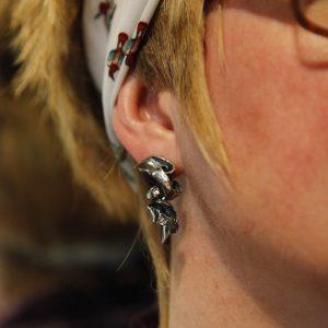Model wears twisty textured silver earrings