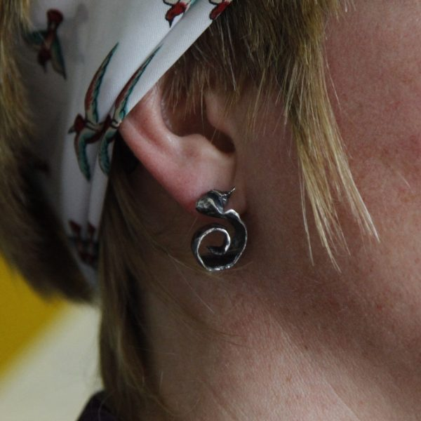 Model wears Unusual silver earrings in shape of a curl and a white headband with ducks on it