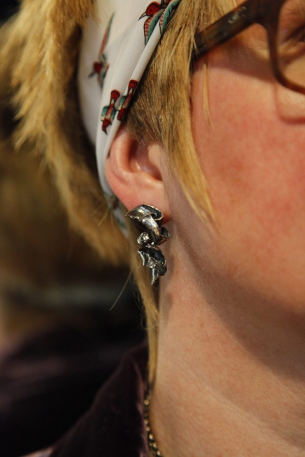 Model wears twisty textured silver earrings