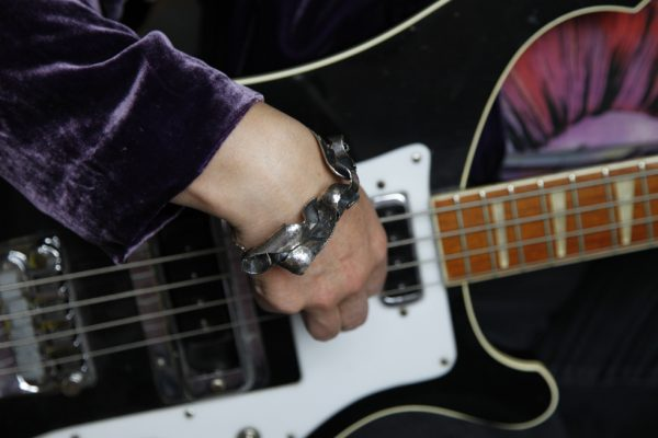 silver bangle statement bracelet model shot with bass guitar