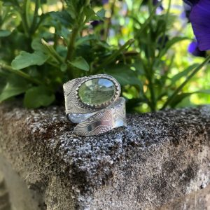 Green Quartz and Silver Ring hand engraved with a swirling pattern on a stone with green plants in the background