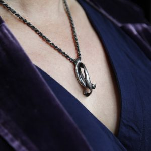Sweet Pea Pod Necklace silver worn by model in navy v-neck dress