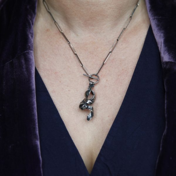Silver T-bar Twist Necklace worn by model wearing a navy blue dress and purple velvet jacket