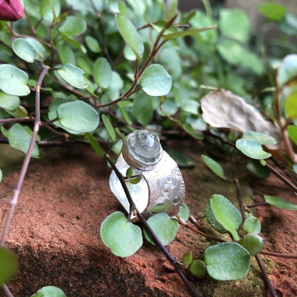 Silver ring set with domed and faceted grey quartz stone, hand engraved with swirls and circles. It rests on a red brick wall surrounded by greenery..