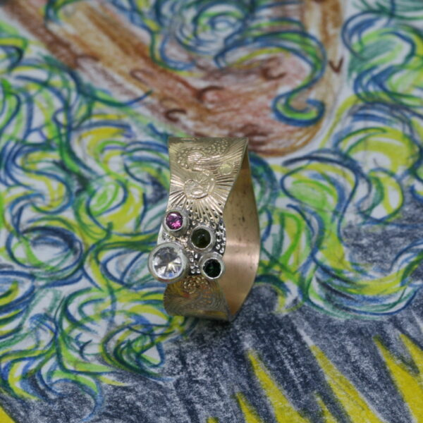 Moonstone tourmaline and Gold Ring hand engraved with swirls, standing on the swirly green and blue sketch that inspired it.